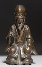 A BRONZE FIGURE OF SHOULAO SEATED ON A WOODEN BASE. China, ca. 17th c. Height 15.7 cm.