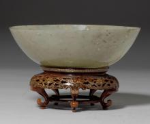 A THIN-WALLED WHITE JADE BOWL ON AN OPENWORK WOODEN BASE.