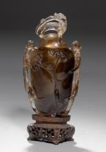 A COVERED VASE OF SMOKY QUARTZ CARVED WITH CHILONGS ON A CARVED WOOD BASE.