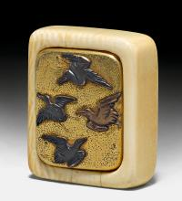 AN IVORY KAGAMI NETSUKE OF GILT METAL WITH FLYING DUCKS IN DIFFERENT METALS.
