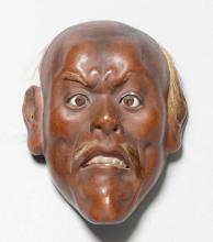 """A MINIATURE WOODEN MASK IN THE FORM OF A """"YASE OTOKO"""" WITH INLAID EYES, PIGMENT AND HAIR."""