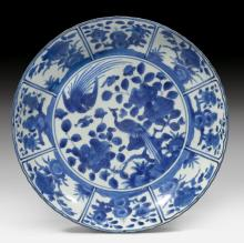 A BLUE AND WHITE ARITA BOWL DECORATED WITH FLOWERS AND TWO PEACOCKS.