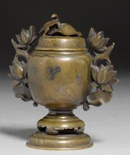 A BRONZE CENSER WITH SILVER INLAY DECORATION AND SCULPTED LOTUS BLOSSOM HANDLES, WITH A COVER SURMOUNTED BY A TURTLE ON A LEAF.