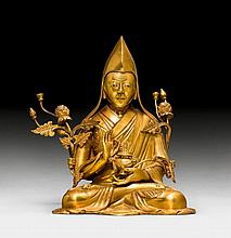 A GILT BRONZE FIGURE OF A HIGH RANKING MONK OF THE