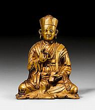 A PARTLY GILT COPPER FIGURE OF A SEATED MONK.