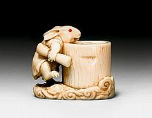 AN IVORY NETSUKE OF THE MOON RABBIT PREPARING