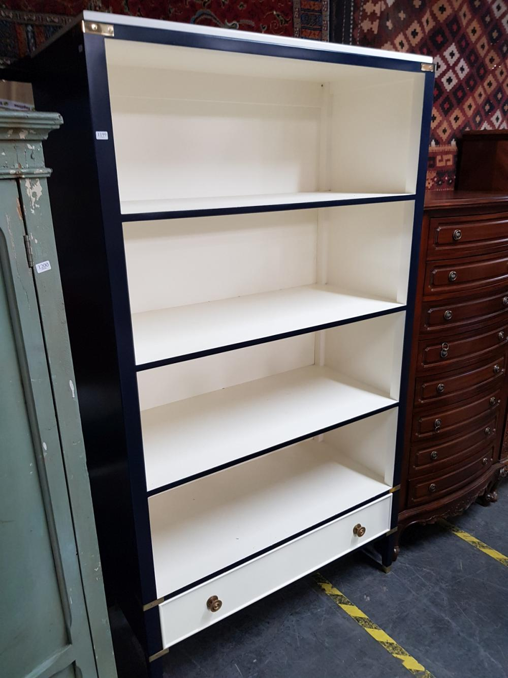 A Navy Bookcase with single white drawer to base on tapering legs with brass hardware, H x 190cm, W x 107cm, D x 48.5cm