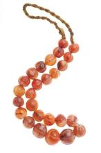 A GRADUATED STRAND OF CARVED AGATE BEADS; 14 - 22mm beads on plaited cord.