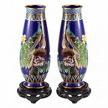 A pair of Chinese cloisonné vases decorated with peacock and peahen on associated timber bases.