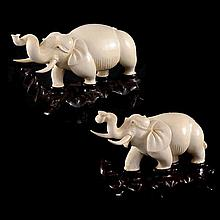 A graduated pair of ivory elephants on shaped stands.