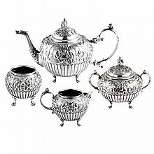 A Dutch silver tea service comprising tea pot, covered sugar bowl, cream jug and another small bowl, chased with inn scenes and flut...