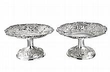 A pair of Victorian silver pedestal dishes moulded with flowers and foliate scrollwork, maker FS/IH? London 1886.