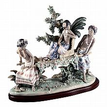 A Lladro figural group of a native girl being carried on a litter, printed and painted marks to base, numbered 30.