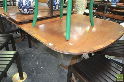 A Georgian Style Mahogany Twin Pedestal Dining Table, c.1950, opening to accept two leaves, reeded apron , all resting on twin tri-f...