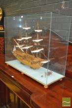Wooden Model Ship of The Royal Caroline (launched 1749) in a glass case (crack to end pane) on a gilt rope edged base