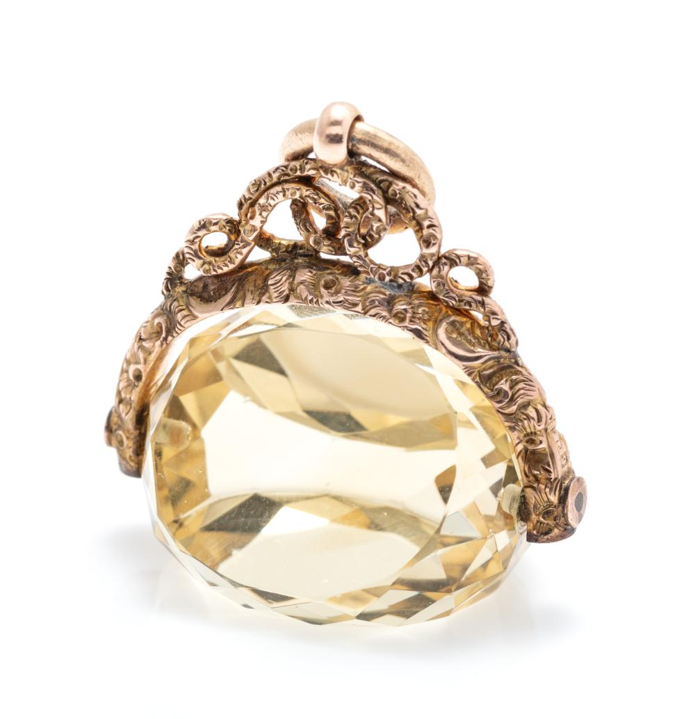 AN ANTIQUE 9CT GOLD SPINNING CITRINE SEAL FOB; scrolling arch suspending a spinning faceted citrine 24 x 18 x 19mm with knot bale ha...