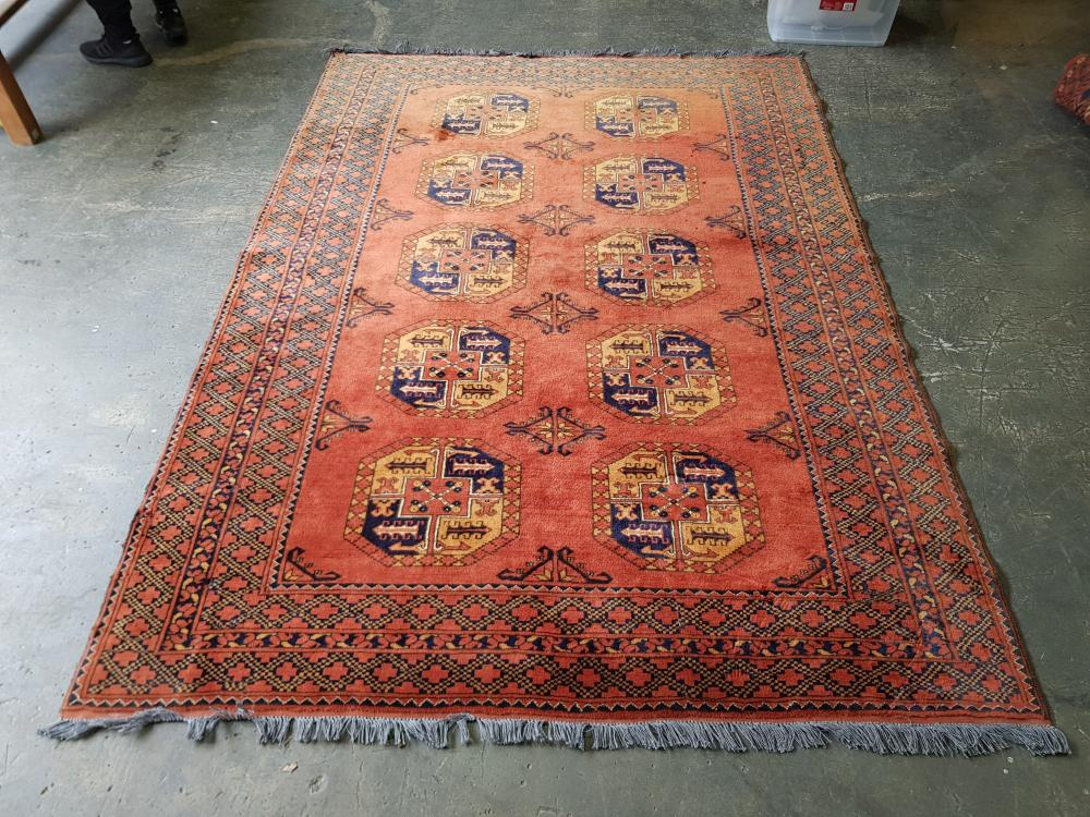 Afghan Turkoman Wool Carpet, with two columns of yellow & blue guls, on a red ground (273x190cm)
