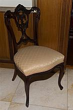 An Edwardian Mahogany shaped back occasional chair with a carved centre swag within a shield on