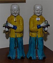 PAIR OF CHINESE FAMILLE JUANE 'LAUGHING BOYS' FIGURES, QING DYNASTY  each well modelled standing holding a basket of auspicious fr...
