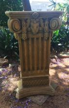 A sandstone finish rectangular pedestal, the top boldly modelled with deeply scrolled corners flanking a goats head above a fluted c...
