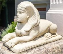 A pair of composite sandstone effect sphinx, length 66cm