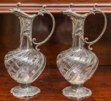 A pair of French Art Nouveau wine ewers. The writhen cut crystal bodies mounted in floral and scrolled silverplate fittings. Ht: 30c...