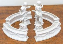 A set of four Continental white porcelain cherubs, height 14cm, together with four arc shaped troughs,