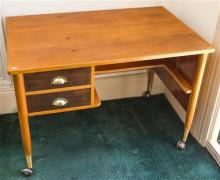 A two drawer timber desk on castors, 75 x 68 x 106cm