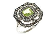 A DECO STYLE PERIDOT AND DIAMOND RING; square cut central peridot surrounded by rose cut diamonds in silver, size L 1/2.