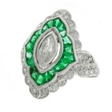A WHITE GOLD DIAMOND AND EMERALD DRESS RING; centring a marquise cut diamond surround by mixed cut emeralds to border and shoulders...