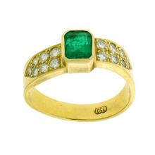AN 18CT GOLD EMERALD AND DIAMOND RING; centring a step cut emerald (some chips and fissures) estimated as 0.90ct between shoulders s...