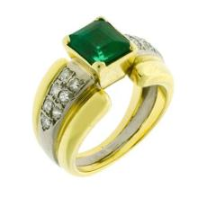 AN 18CT GOLD EMERALD AND DIAMOND RING; centring a step cut fine green emerald estimated as 1.80ct (abraded) to 14 single cut diamond...