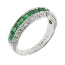 AN 18CT WHITE GOLD HALF HOOP EMERALD AND DIAMOND RING; channel set with square cut emeralds totalling estimated 0.90ct, to sides set...