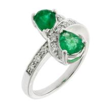 AN 18CT WHITE GOLD EMERALD AND DIAMOND RING; featuring 2 pear shape emeralds totalling an estimated 1.17ct adjacent to 12 round bril...