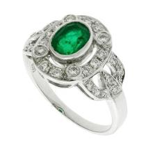 AN 18CT WHITE GOLD EMERALD AND DIAMOND RING; deco style with central emerald estimated as 1.08ct to surround and shoulders set with...