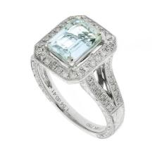 AN 18CT WHITE GOLD AQUAMARINE AND DIAMOND RING; emerald cut pale aquamarine of approx. 1.54ct four claw set above surround and split...