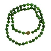 A JADE BEAD NECKLACE; 10mm round dark green nephrite jade beads to a 9ct gold clasp, length 70cm.