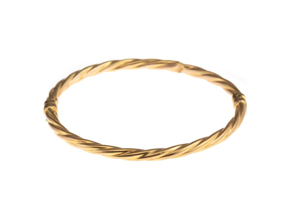 A 9CT GOLD HOLLOW TWIST FORM BANGLE; fitted with a safety clip, internal dim. 58 x 55mm, Italian manufacture, wt. 4.78g.