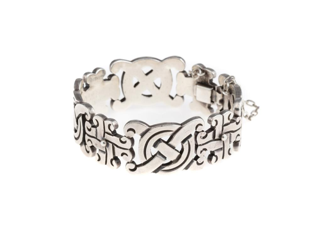 A MEXICAN SILVER BRACELET; 2cm wide bracelet of geometric motifs to a box clasp with safety chain, length 19.5cm, wt. 75.6g.