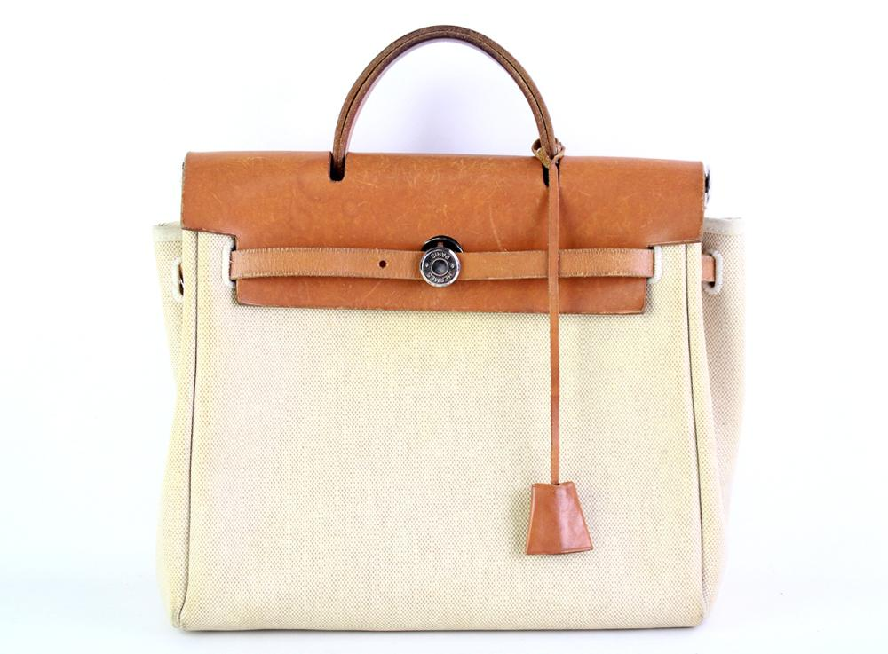 A VINTAGE HERMES HERBAG 2 IN 1 BACKPACK; in beige toile canvas and tan leather with chrome metal hardware including padlock and 2 ke...