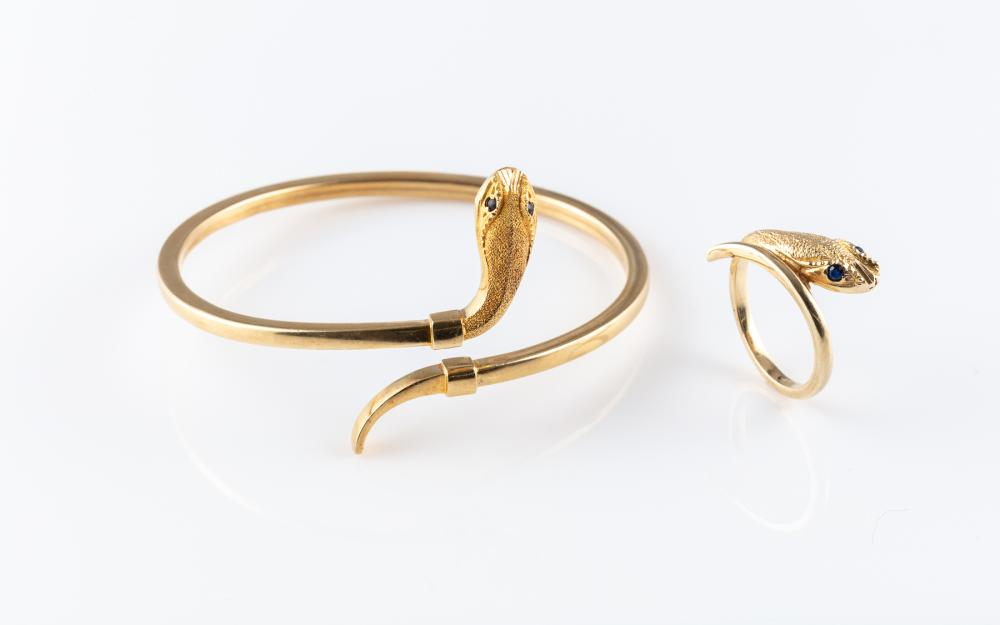 A 14CT GOLD SNAKE BANGLE AND RING SUITE; ring size N 1/2, bangle internal circ. 17cm, both by pass design with sapphire eyes, total...