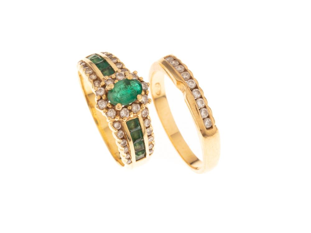 AN 18CT GOLD EMERALD AND DIAMOND RING SUITE; main ring an oval emerald and 10 round brilliant cut diamond cluster to shoulders each...