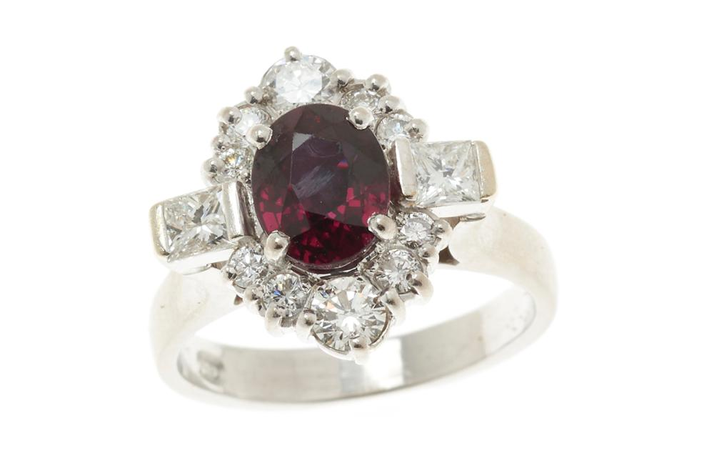AN 18CT WHITE GOLD RUBY AND DIAMOND DRESS RING; centring a deep red oval cut ruby estimated as 1.30ct (slightly abraded) adjacent to...