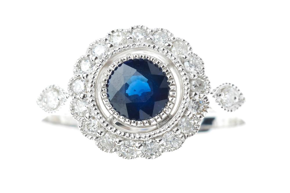 AN 18CT WHITE GOLD SAPPHIRE AND DIAMOND CLUSTER RING; milligrain set with a 1.21ct dark blue sapphire to surround and shoulders set...