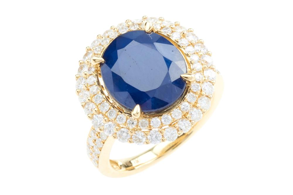 AN 18CT GOLD SAPPHIRE AND DIAMOND RING; centring an  approx. 7.90ct treated blue sapphire, to a 2 row border and shoulders set with...