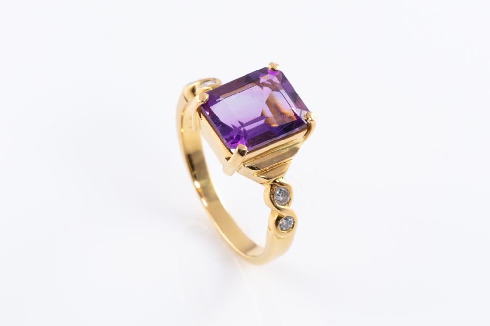 AN 18CT GOLD AMETHYST AND DIAMOND RING; centring a step cut amethyst of approx. 3.40ct to 4 round brilliant cut shoulder diamonds to...