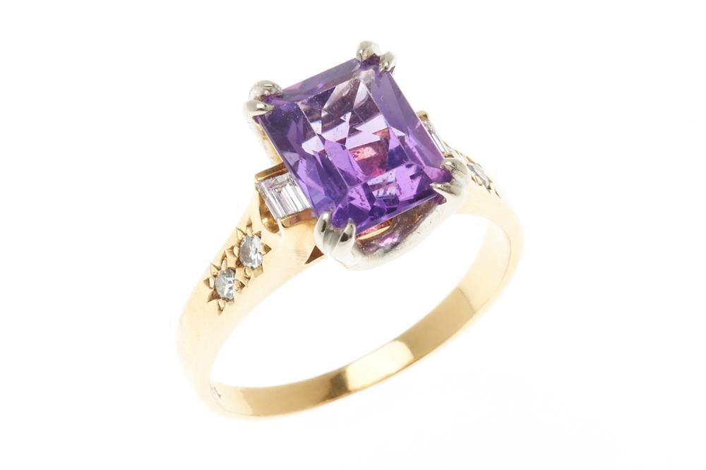 AN 18CT GOLD AMETHYST AND DIAMOND RING; centring a step cut amethyst to shoulders set with 4 single and 2 baguette diamonds, size Q,..