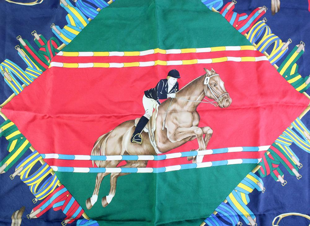A GUCCI EQUESTRIAN SILK SCARF; featuring show jumping on red, green and navy ground, 88 x 88cm.