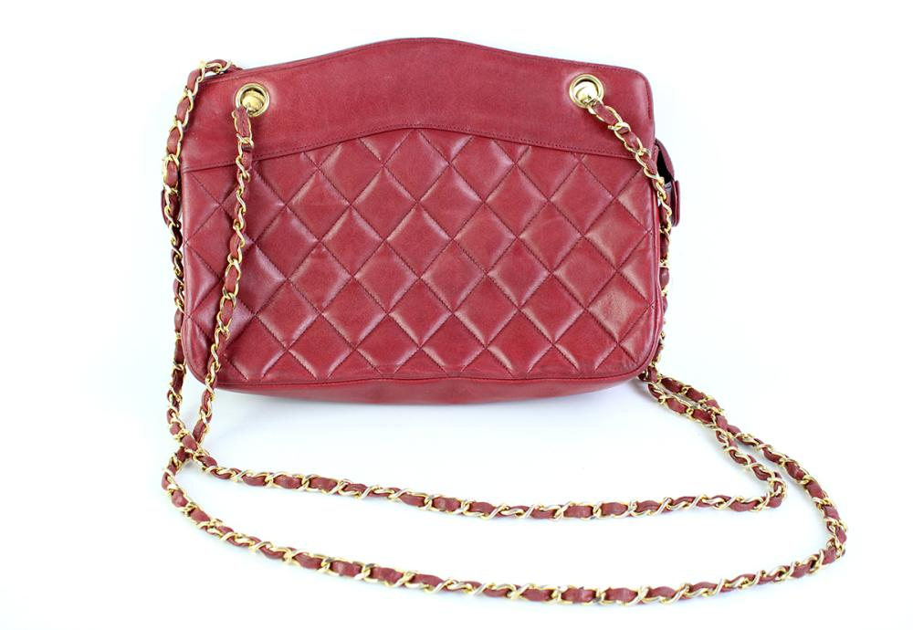 A VINTAGE CHANEL QUILTED BURGUNDY LAMBSKIN LEATHER HANDBAG; with gilt metal hardware and chain handle, with black leather interior a...
