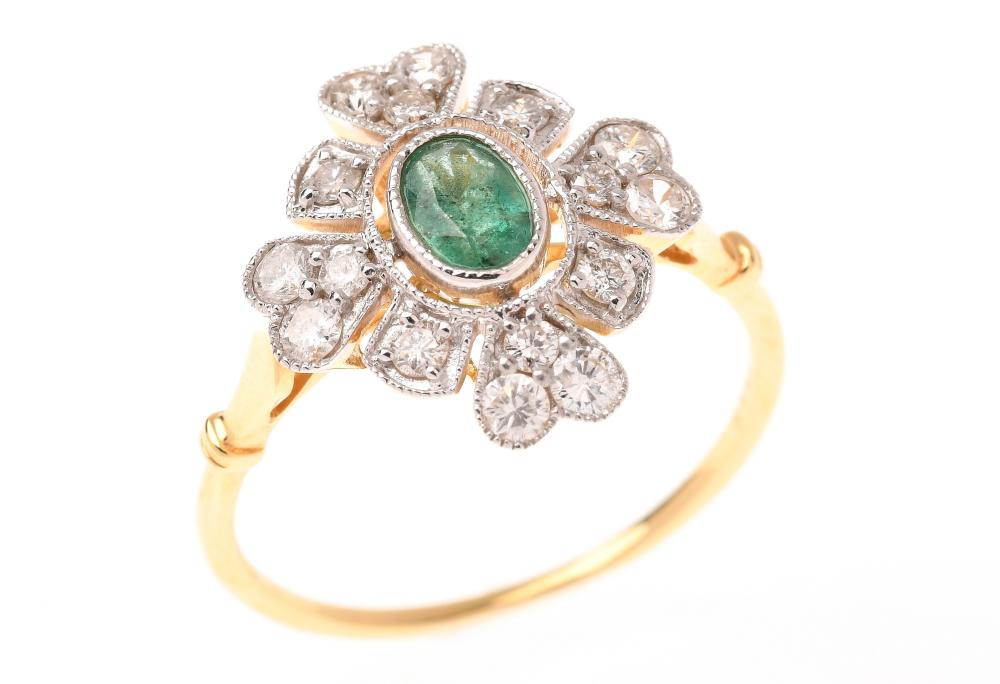 AN 18CT GOLD EMERALD AND DIAMOND RING; centring an oval cut emerald of 0.38ct to quatrefoil surround set with 16 round brilliant cut...